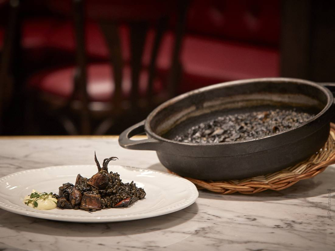 Baby cuttlefish in squid ink rice with aioli